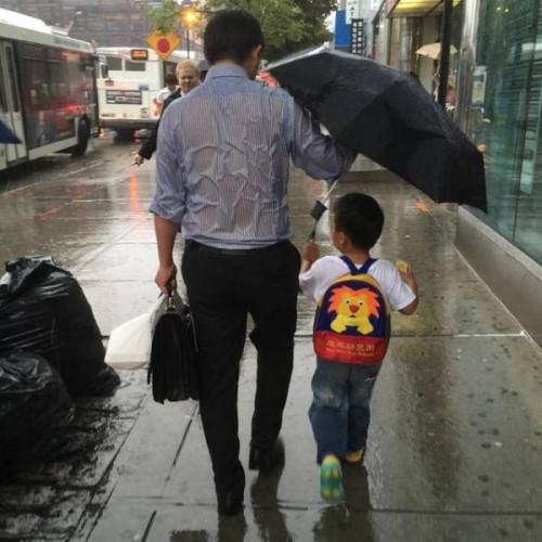 子供のために傘をさす父親